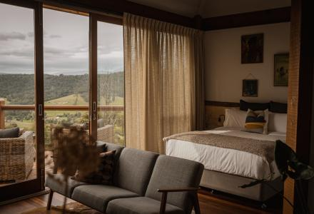 Inside of the cabin with bed, lounge and mountain views
