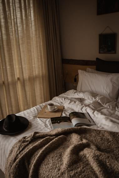book and tea on unmade bed