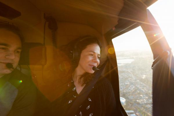 A couple looking out of a helicopter window onto Melbourne city