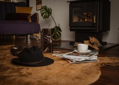 hat, tea and books on floor by the fire