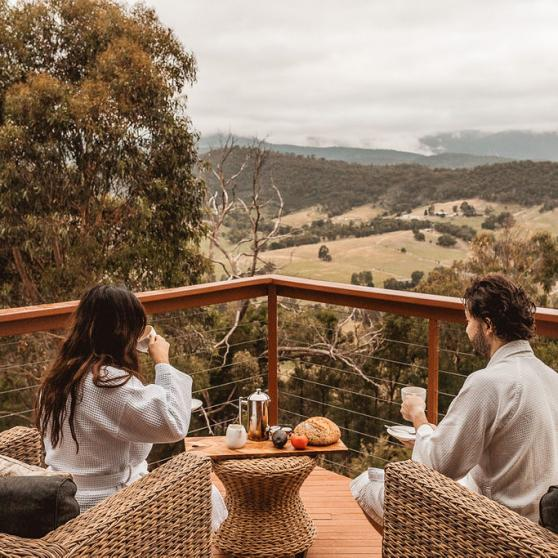 A couple sitting on a balcony looking at mountain ranges